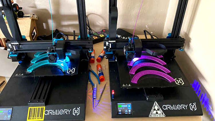 Two 3D printers producing PPE mask components